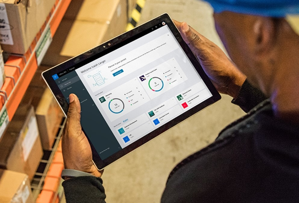 Image of person holding a tablet with the Office 365 dashboard on it.